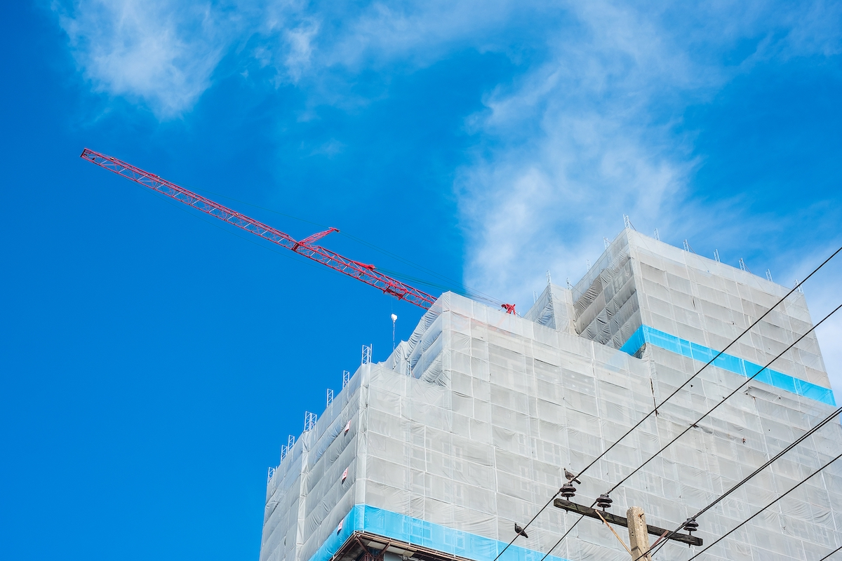 High rise Building Construction site with crane on blue sky background