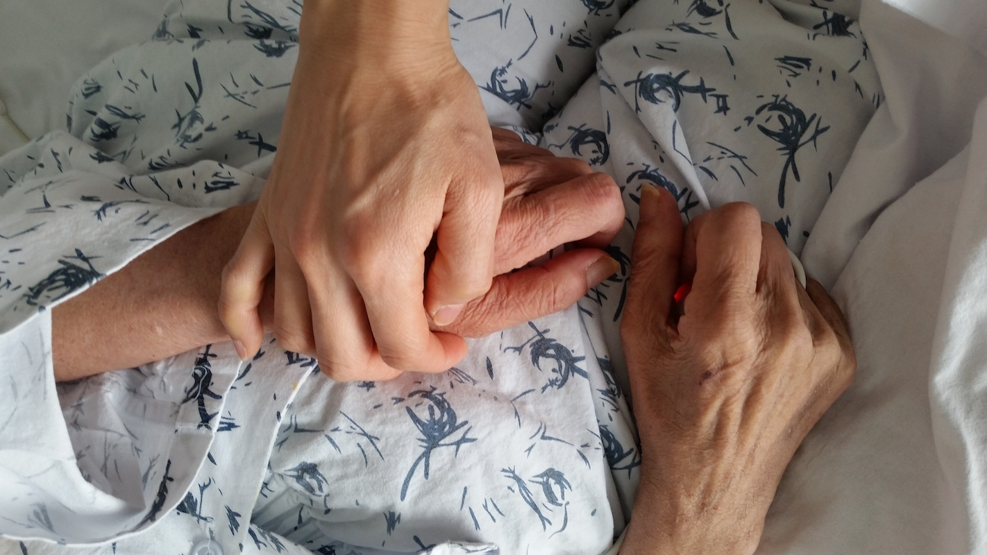 holding-elderly-family-members-hand-in-hospital-during-end-of-life-care_t20_roJeLd